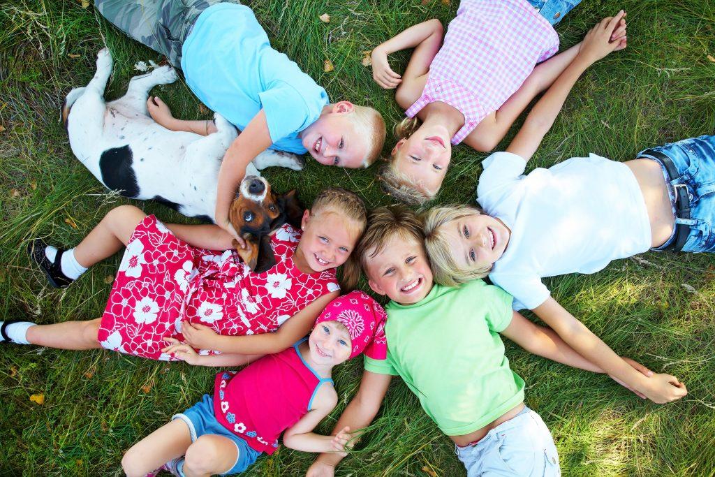 תמונה של ילדים שוכבים על הדשא מחבקים כלב